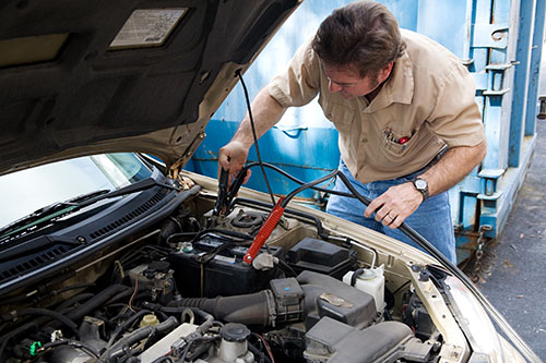 man checking electrical component of car engine
